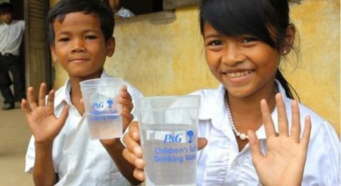 Niños con agua obtenida tras la aplicación de los parquetes purificadores (fuente: P&G)