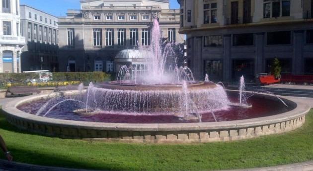La fuente de la plaza de Escandalera teñida de rosa.